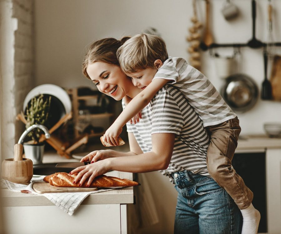 preparation of a family breakfast. mother and child son cut bread  in morning