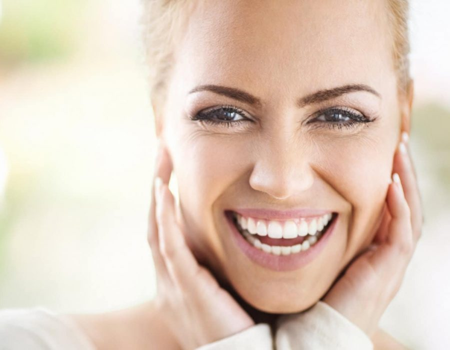 Closeup portrait of an attractive mid 30's woman gently touching her neck and smiling while looking at the camera and sincerely smiling. Blurry green background.